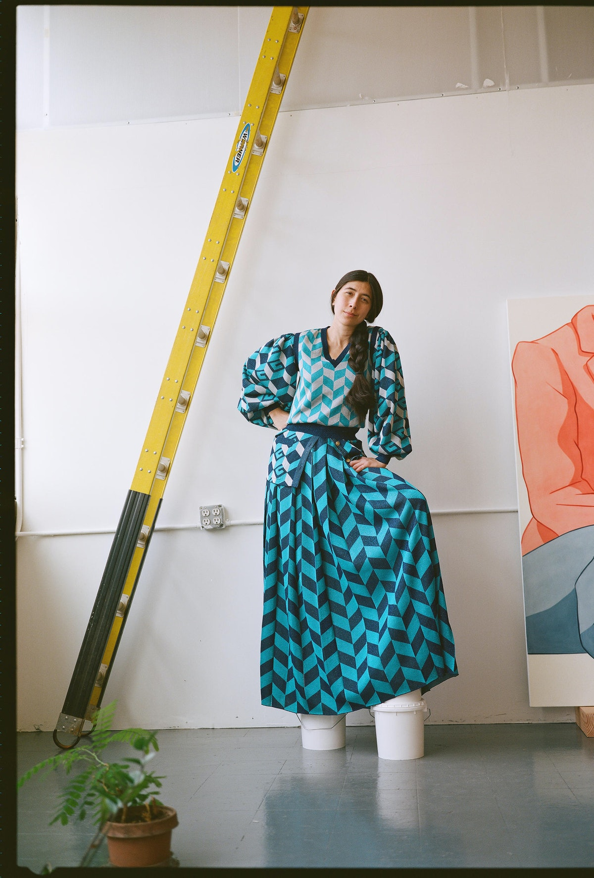 Ivy Haldeman wears a Gucci blouse, vest, and skirt; her own shoes in her studio.
