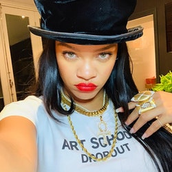 selfie of rihanna wearing red lipstick, gold jewels, and a top hat