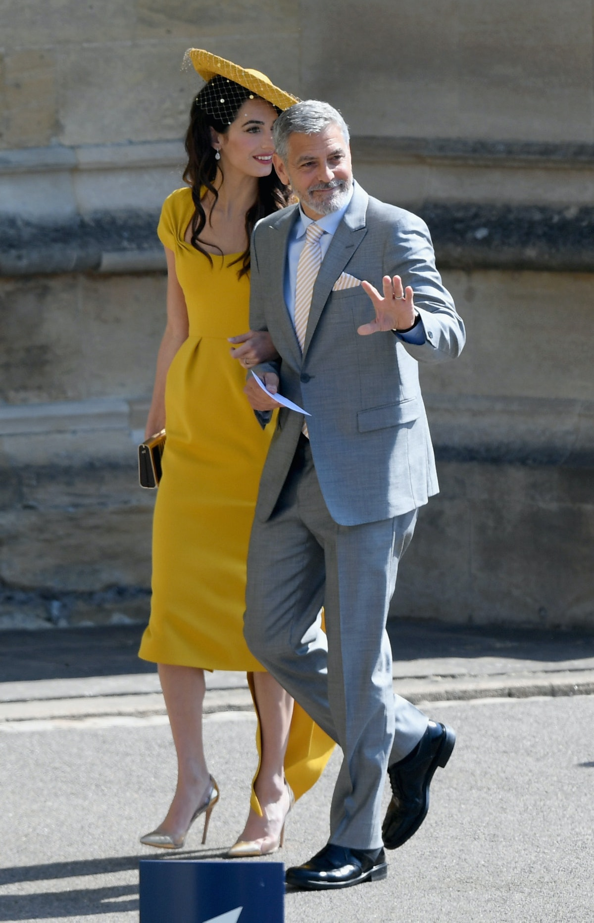 Amal Clooney in a yellow gown and hat, George Clooney in a gray suit