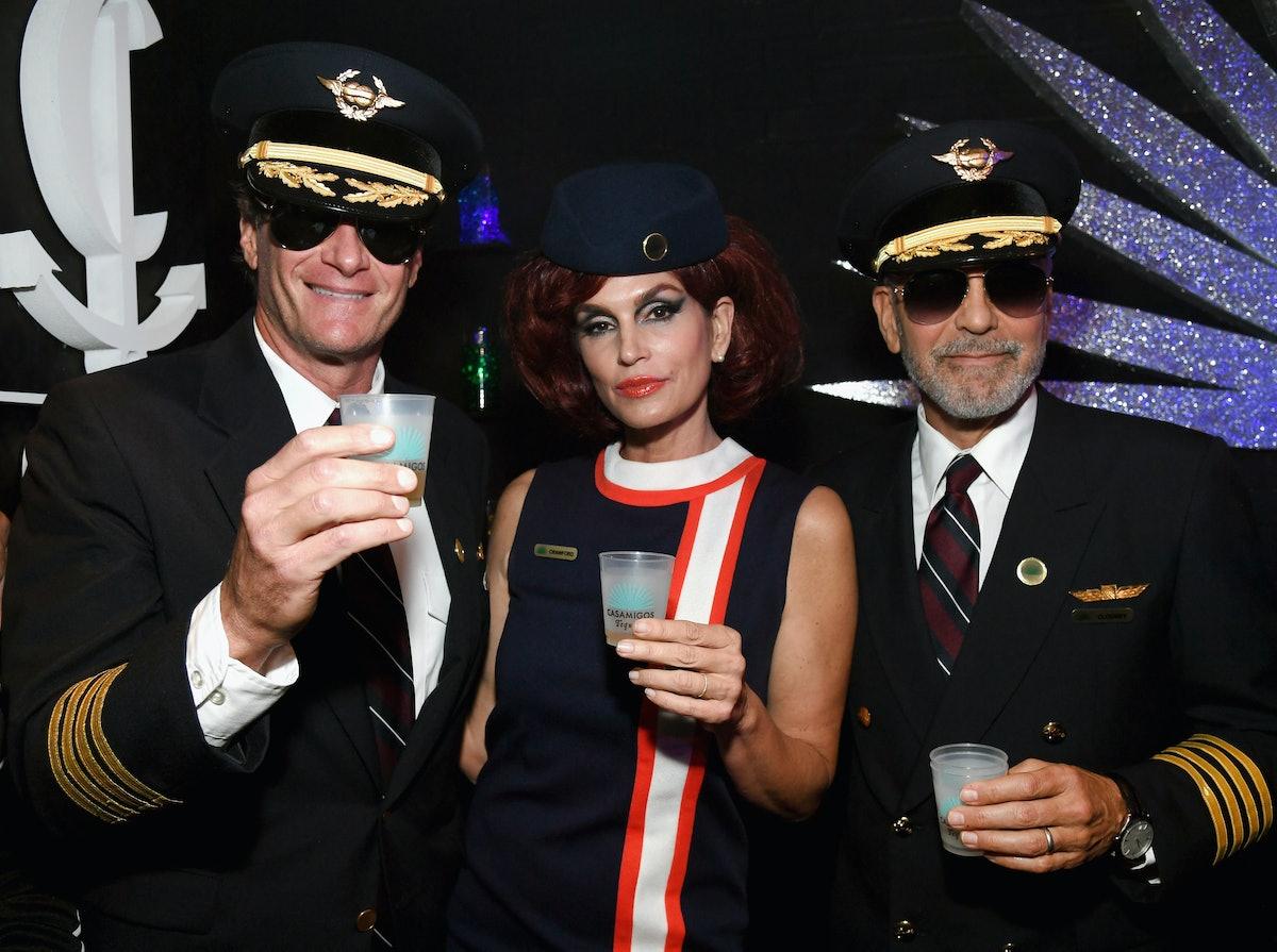 Rande Gerber in a pilot uniform, Cindy Crawford in a flight attendant uniform, George Clooney in a pilot uniform