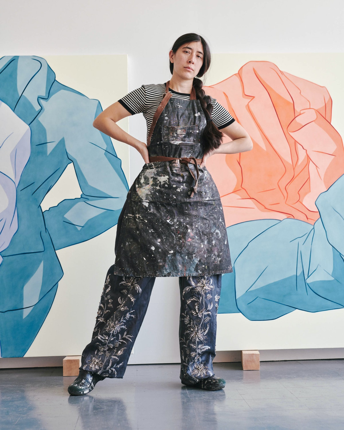 Ivy Haldeman Louis Vuitton T-shirt and pants; her own apron and shoes in front of two paintings.