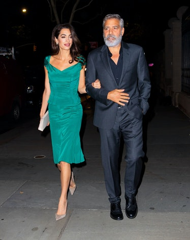Amal Clooney in a green dress, George Clooney in a navy suit wearing a big beard