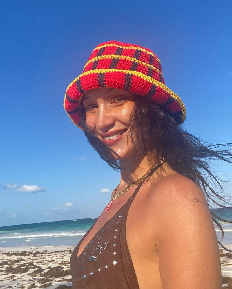 a photo of bella hadid smiling on the beach with a red hat on and dark hair