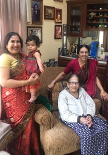 The author wears a sari, holding her toddler daughter. Her mother and grandmother are both pictured as well.