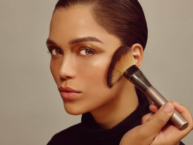 Woman wearing makeup and using makeup brush