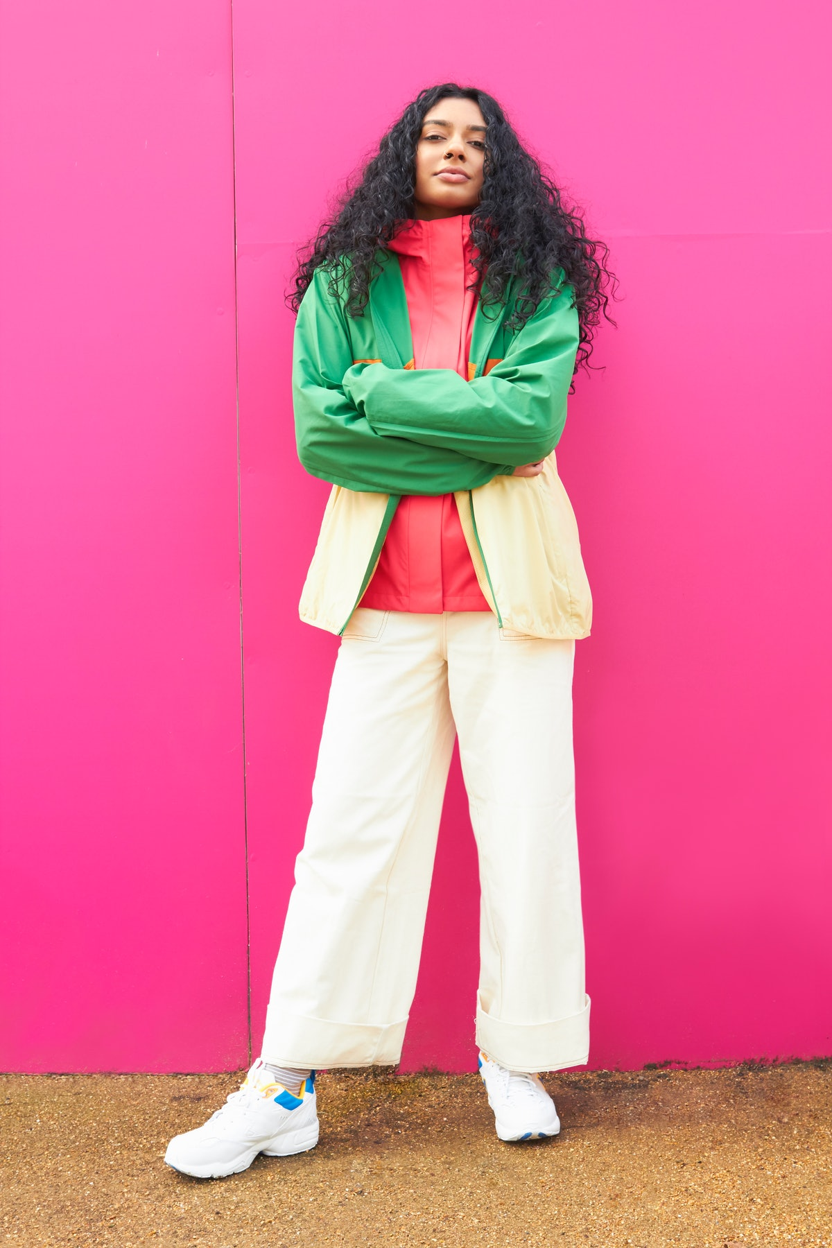 Young woman crossing her arms with a pink background, since she's an intense Cancer.