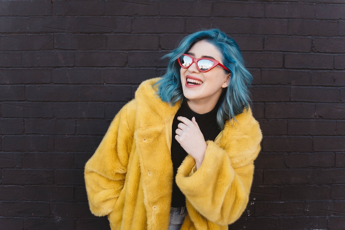 Smiling young woman with blue hair and yellow coat, having the best week of June 14, 2021, per her zodiac sign.