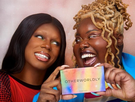 Two Black models wearing makeup and holding up a Pride beauty product from queer-owned beauty brand Fluide Beauty.