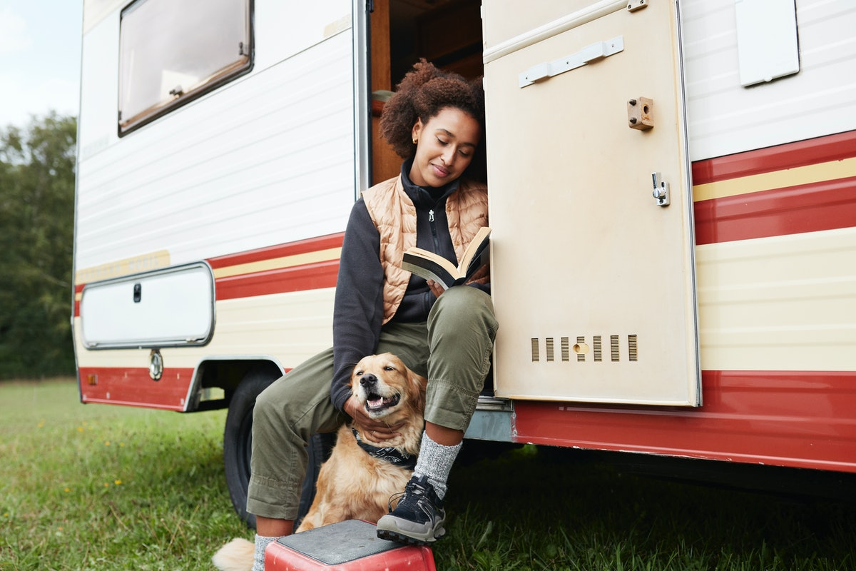 Young woman in a motor van with her dog, posing for a fun Instagram.