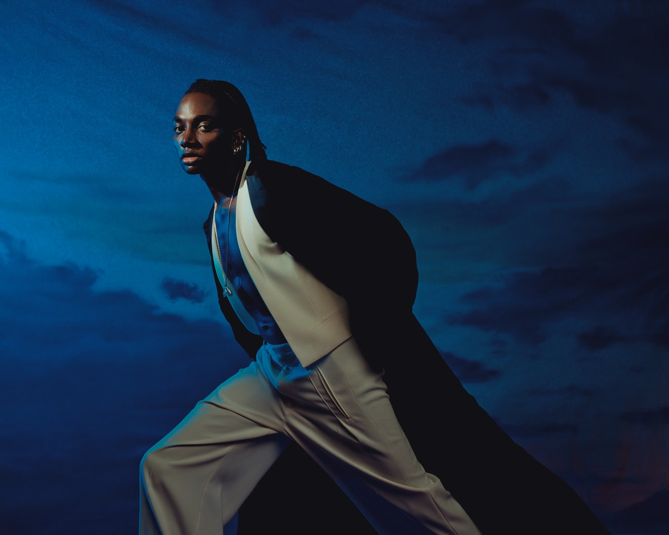 Rickey Thompson stands against a dark sky background wearing a long, open black Chanel coat and whit...