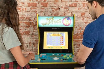 Two people playing Arcade1Up's The Simpsons cabinet video game