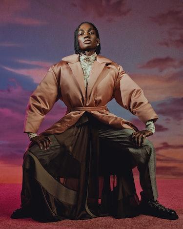 NYLON cover star Rickey Thompson poses sitting down in a light pink Giambattista Valli coat against ...