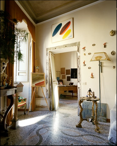 a living room in Rome with art and a hand painted lamp visible