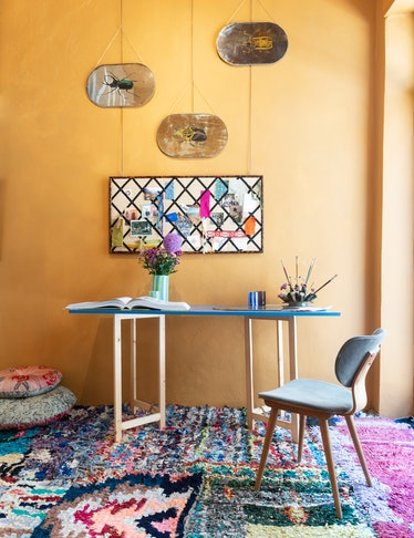 Over a patchwork of vintage rugs, a custom table and chair hold an array of Taschen books and cups b...