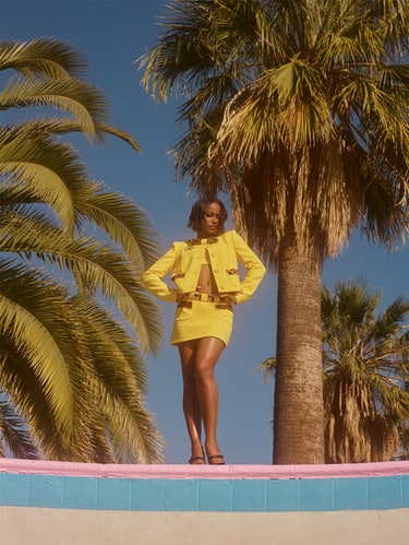 'Zola' star Taylour Paige stands outside in front of palm trees wearing a yellow matching Moschino j...