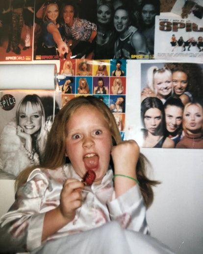 Adele as a young child, posing in front of her Spice Girls posters