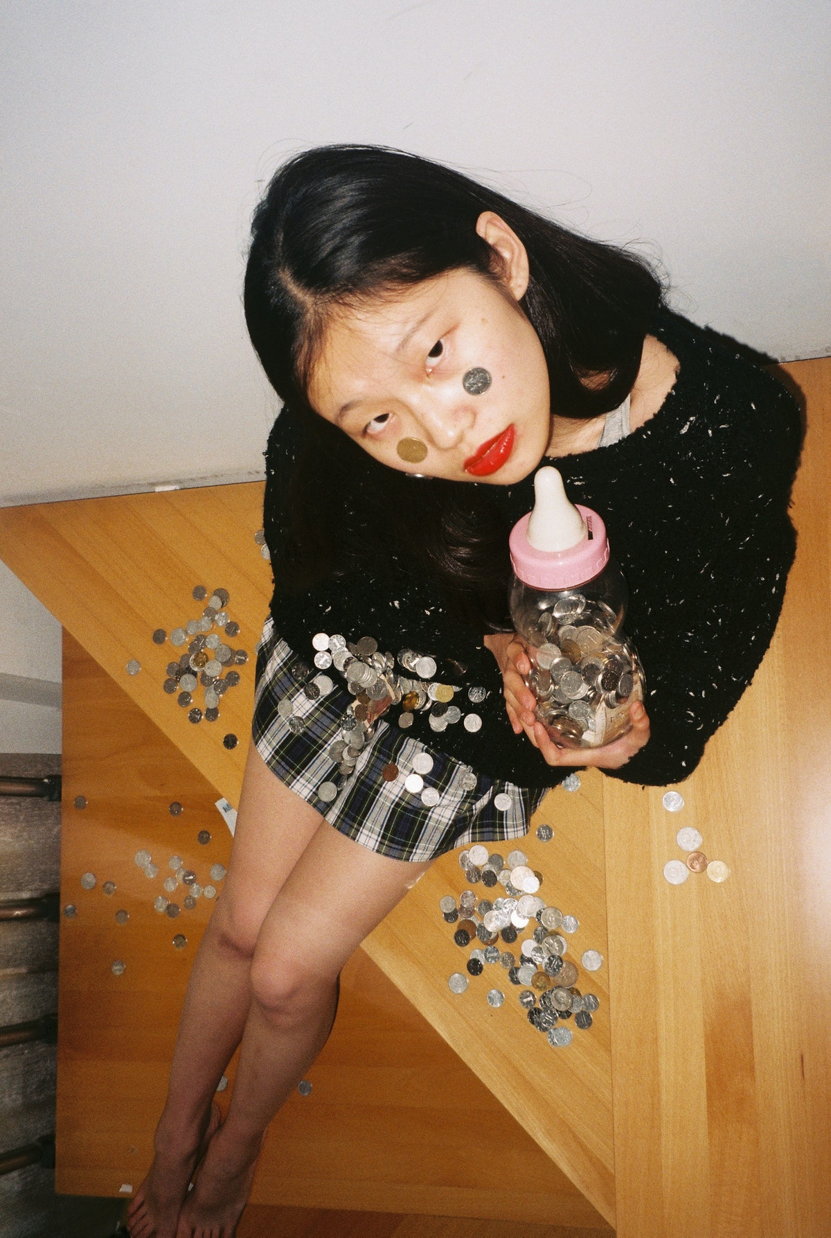 Young woman playing with coins and a baby bottle to show how old she is mentally, according to her z...