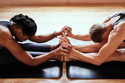 man and woman stretching on mat for partner yoga