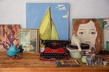 typewriter and paintings on a desk