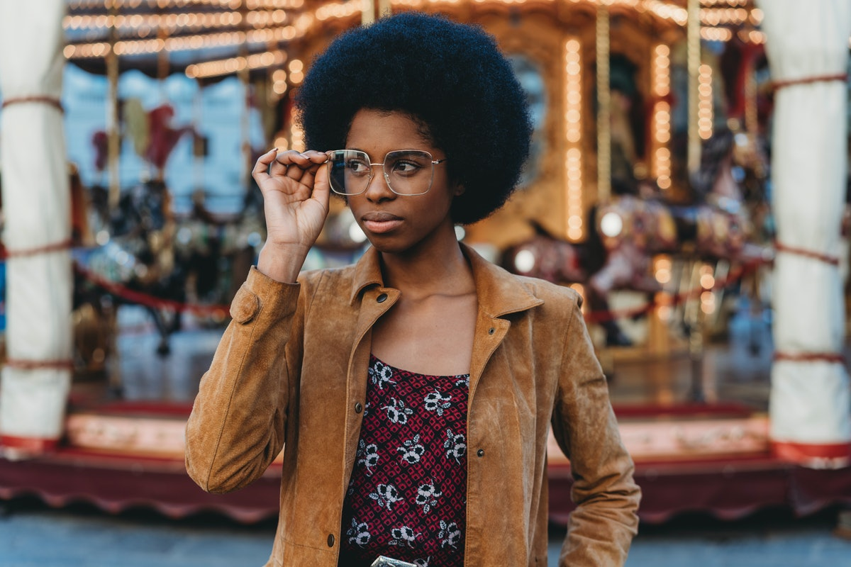 Young woman with glasses in front of a carousel, who's older & mentally more mature for her age, acc...