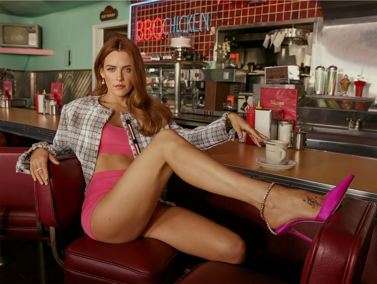 'Zola' star Riley Keough sits at the counter of a diner wearing a plaid jacket over pink shorts and ...