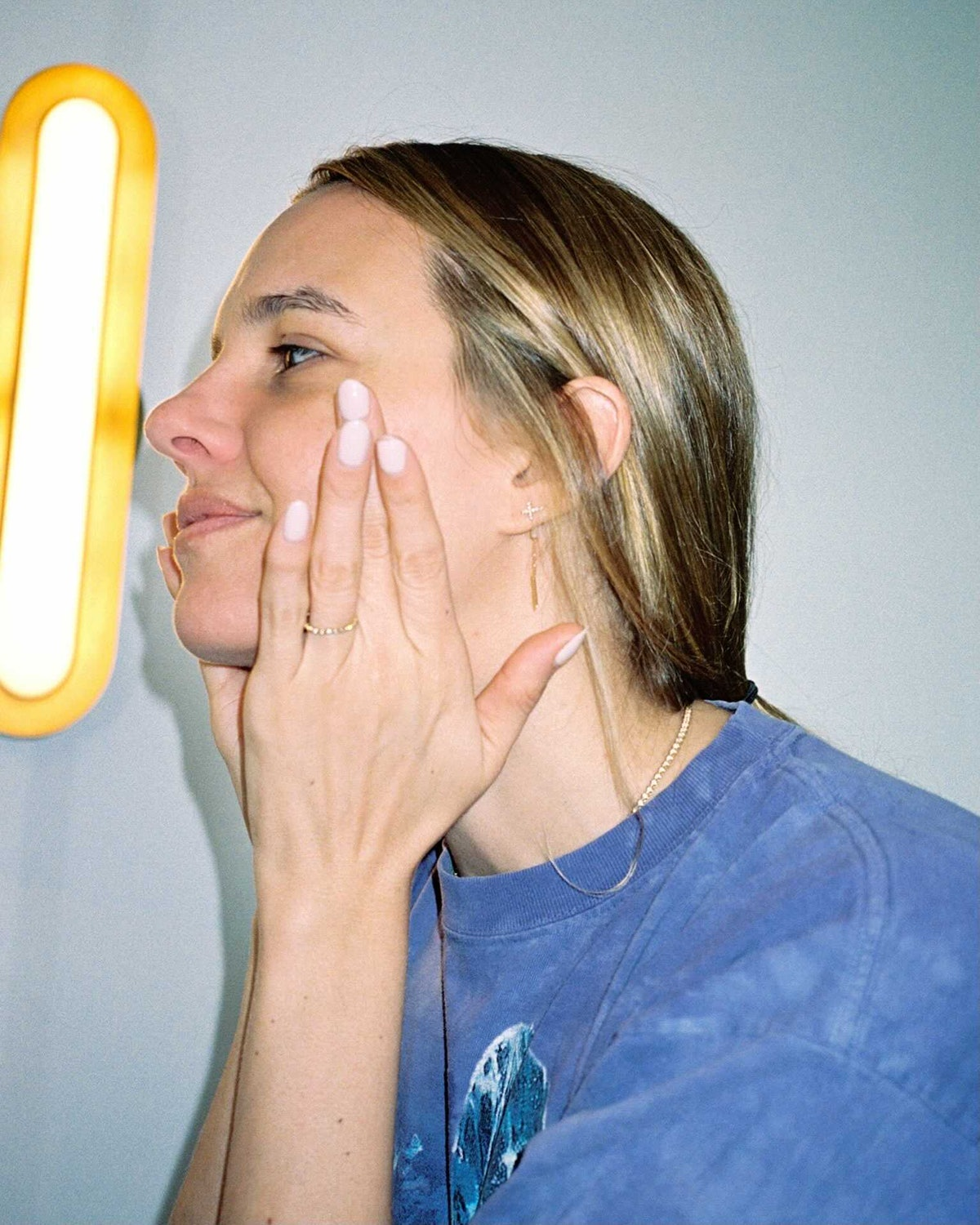 Tracy Dubb washes her face in front of a modern light fixture