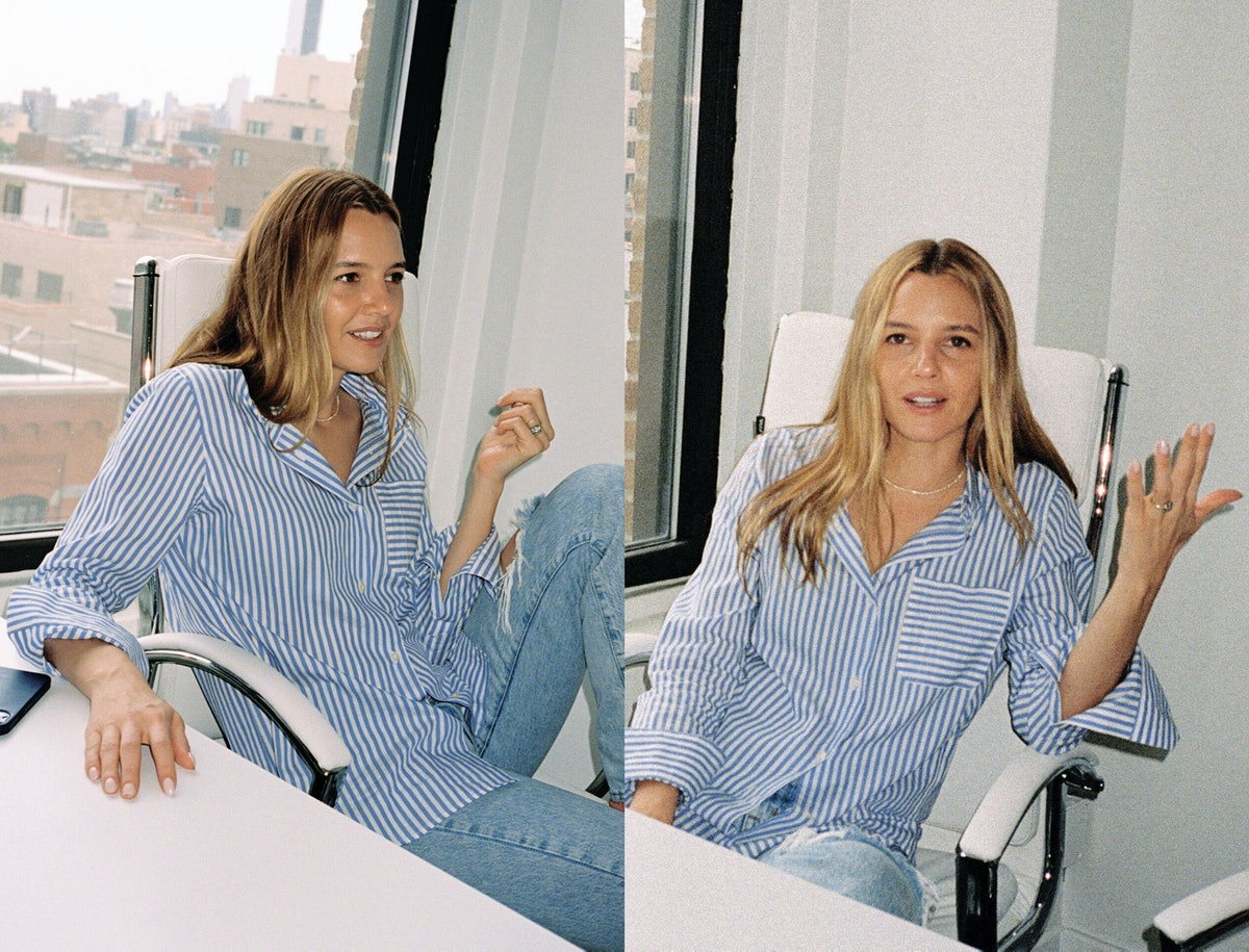 Tracy Dubb, a co-founder of Isla Beauty, sits at her desk wearing a striped button down shirt and jeans