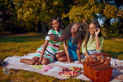 Waeve wig models on-set having picnic