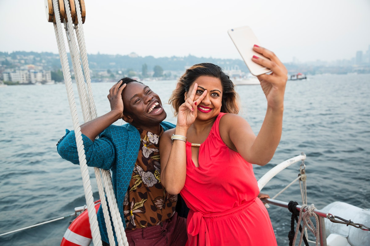Young couple taking a funny selfie on a boat before posting it on Instagram with boat puns, sailing puns, ship puns.