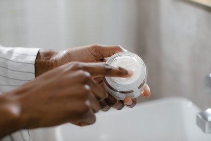 Woman applying cream from a jar