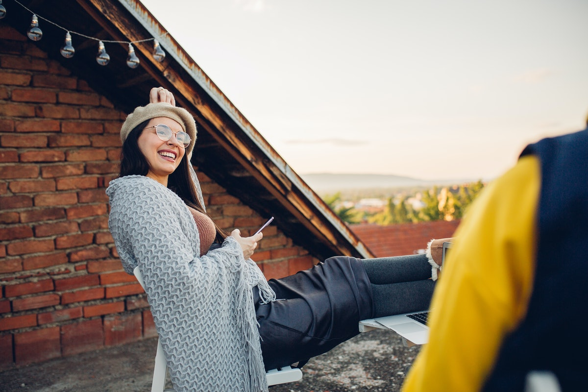 Young woman laughing on a rooftop, thinking of a funny comment to post on her partner's Instagram.