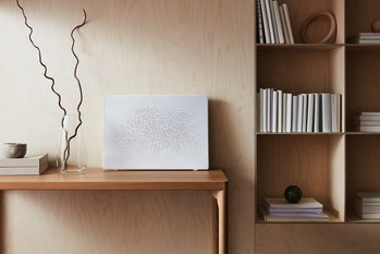 a white picture frame leans against a light-colored wood wall
