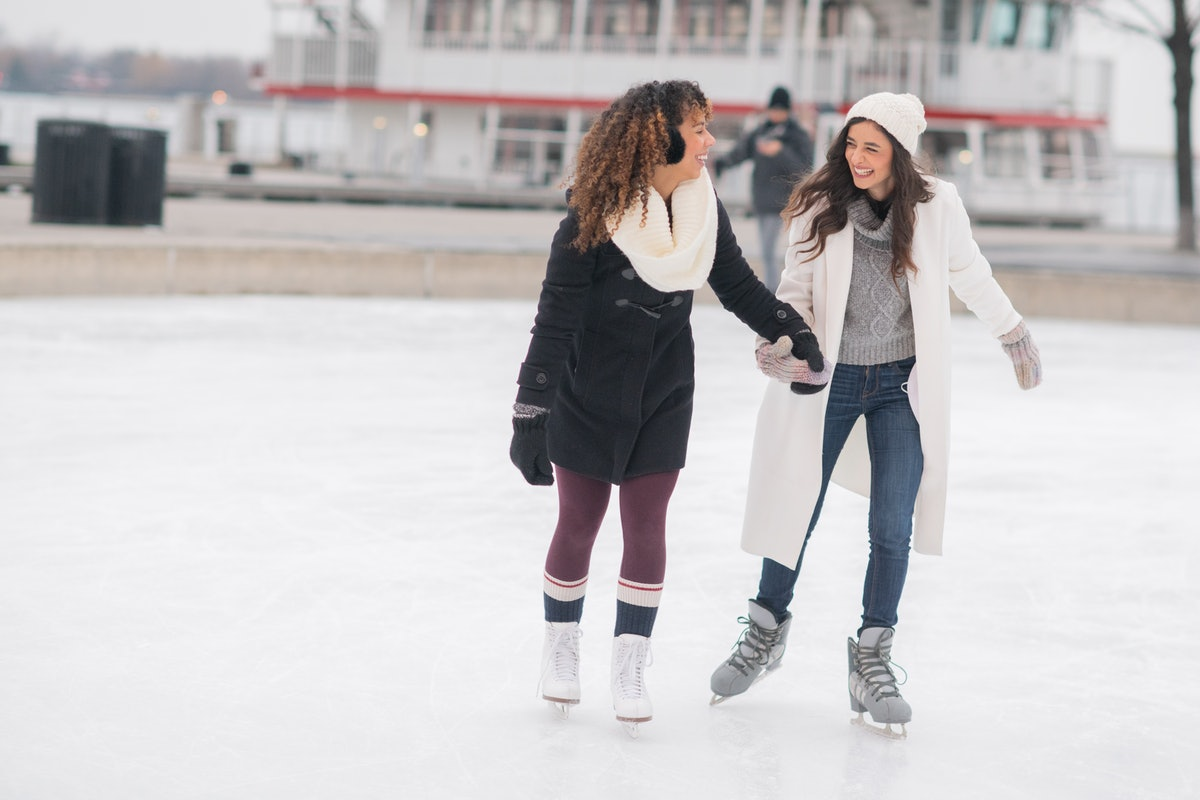 Young couple holding hands & ice skating, in need of puns for Instagram captions.