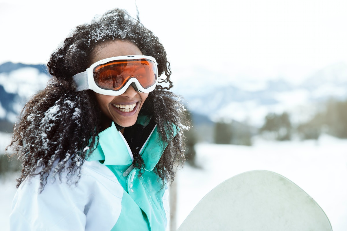 Young woman smiling in the snow, getting ready to snowboard before posting a picture on Instagram with a fun caption.