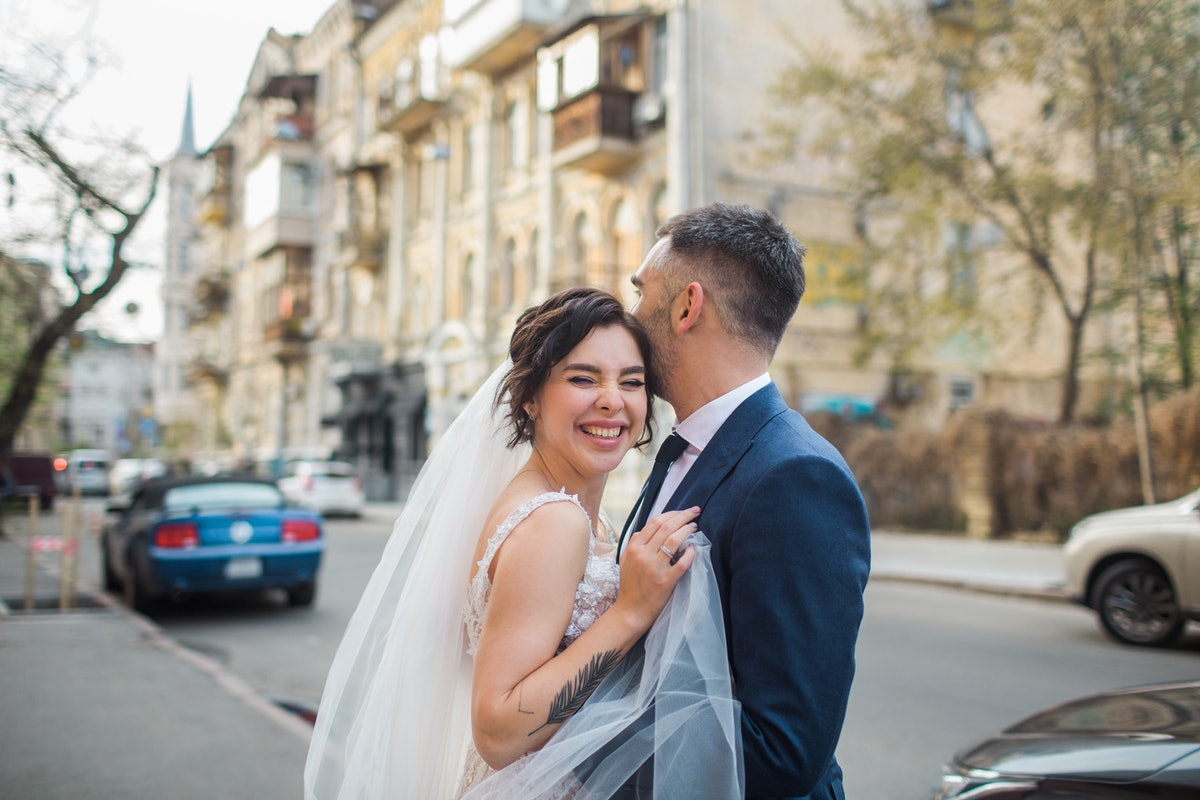 Young bride & groom smiling in the street on their wedding day, in need of a funny wedding hashtag.