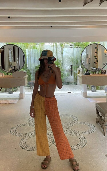 Kendall Jenner in orange and yellow lounge pants.