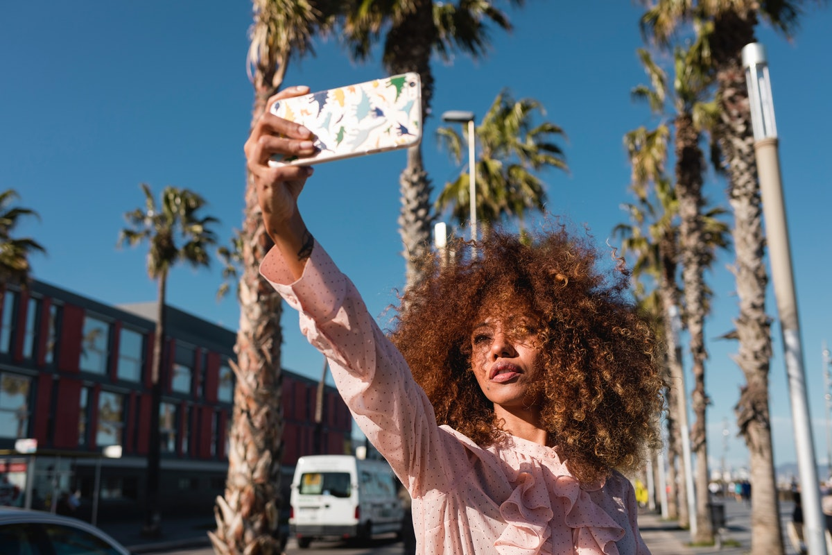 Young woman taking an elegant selfie with palm trees in the background, to post on Instagram with a ...