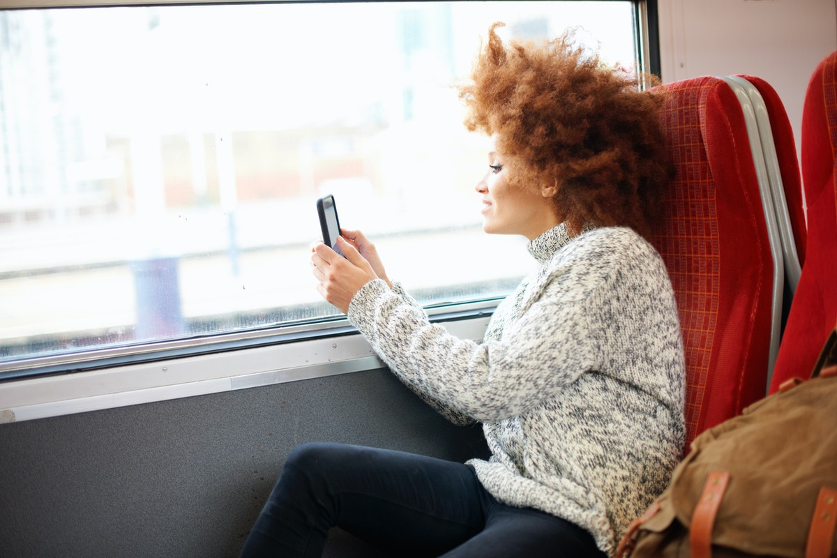 Young woman sitting on a train, taking a picture through the window before posting it on Instagram with a train track caption, quote.