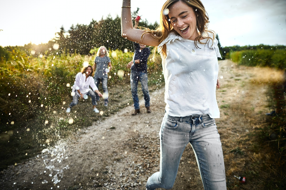Young woman on a dirt road with her family behind her before posting a picture on Instagram with a f...