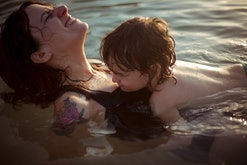 toddler laying on his mom in the sea