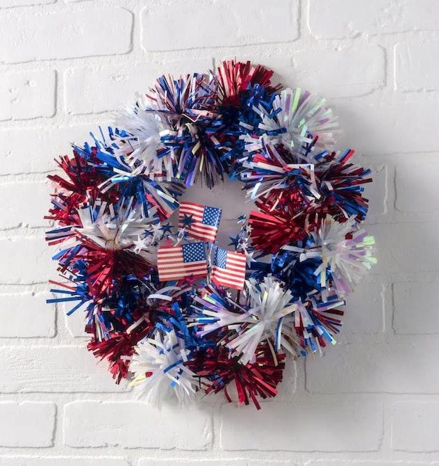 A pom pom wreath is a 4th of July craft for kids to enjoy.