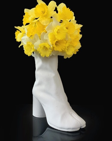 a vase shaped like a boot filled with daffodils