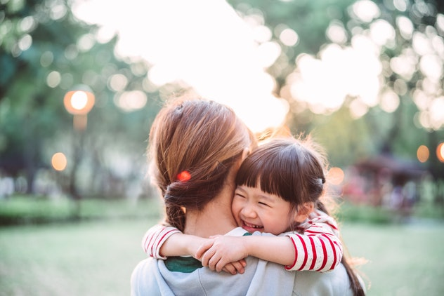 Back view of young mom carrying her smiling daughter in the park