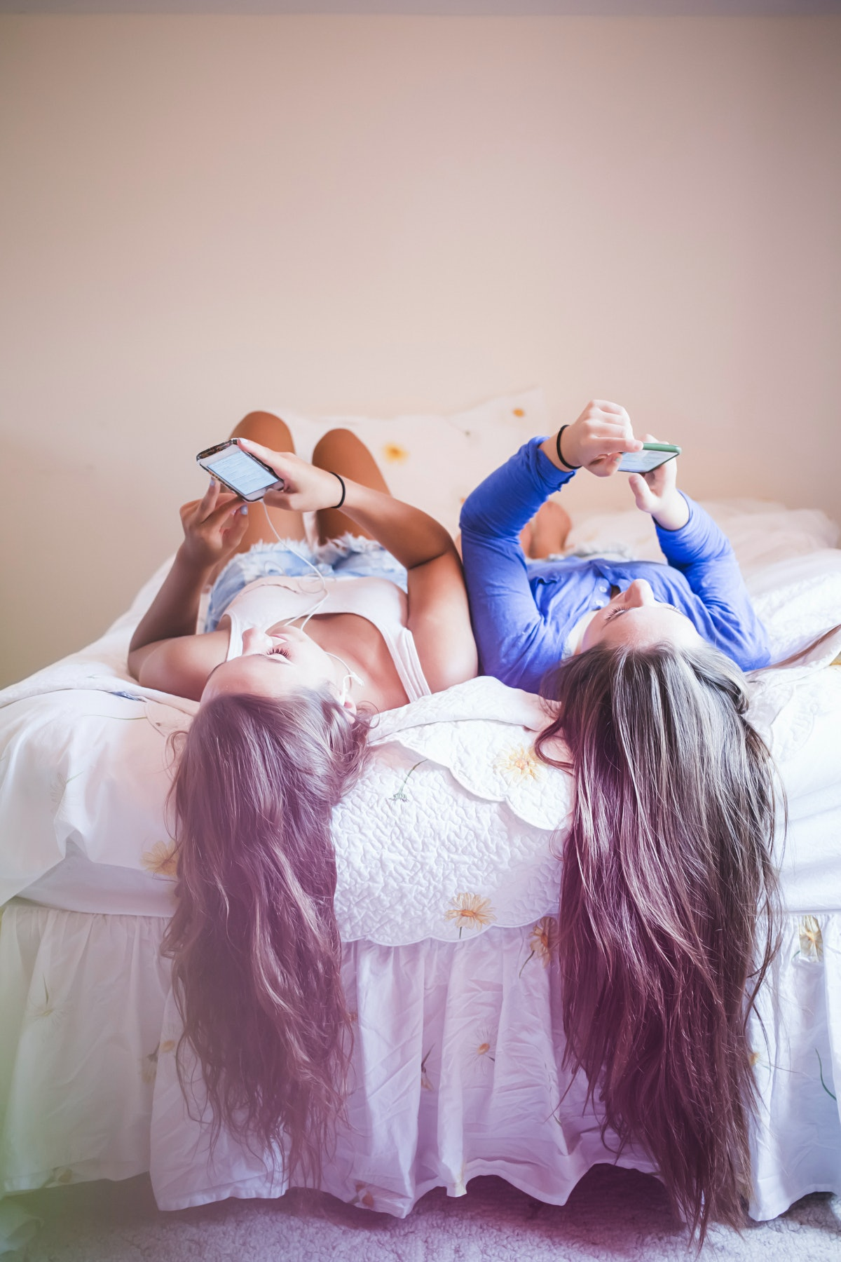Young girls laying upside down on a bed looking at their phones, thinking of what lazy Instagram captions to post.
