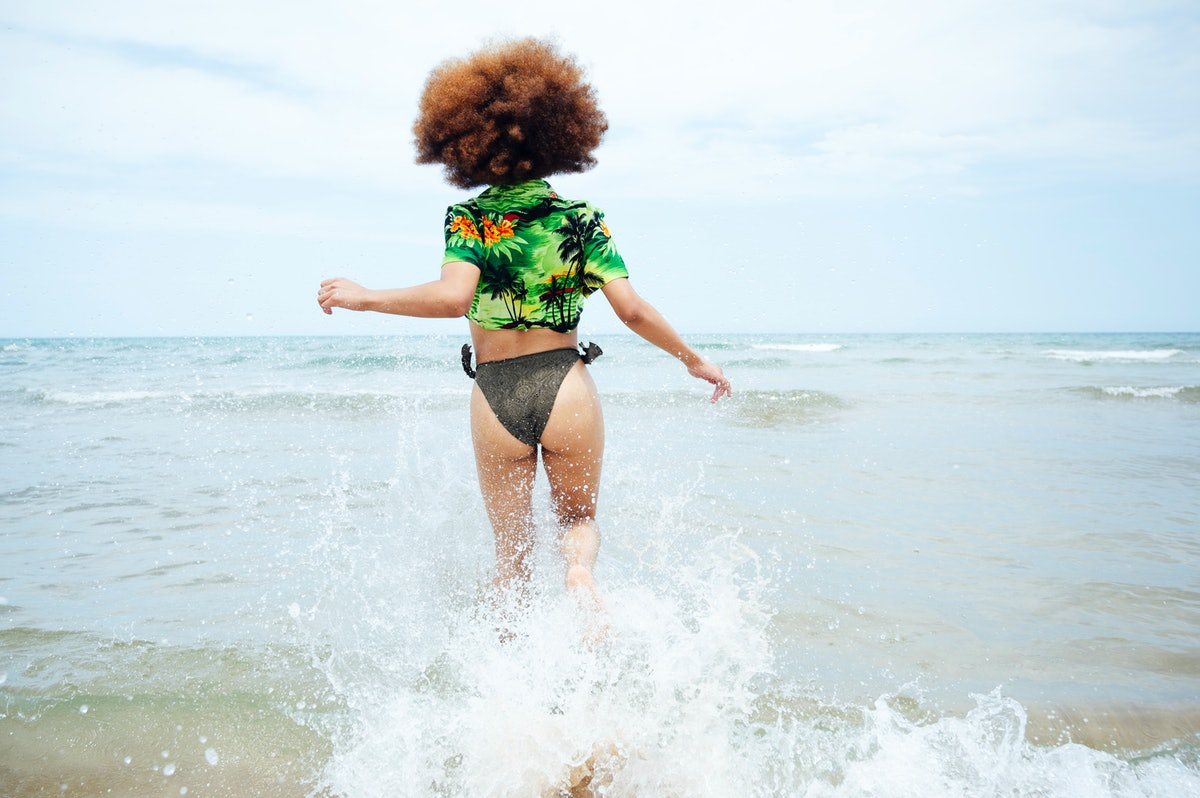 Young woman running into the water on the beach before posting a picture on Instagram with a tropical quote or palm tree caption.