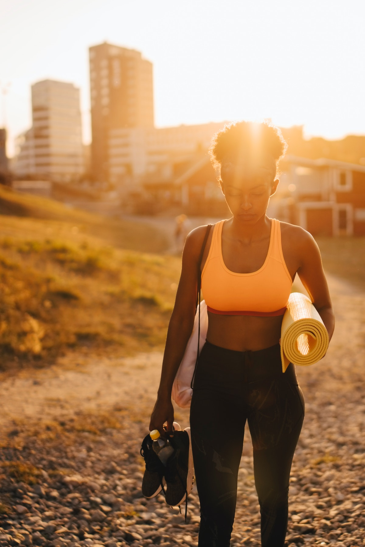 Young woman on her way to do unique summer fitness activities at sunrise.