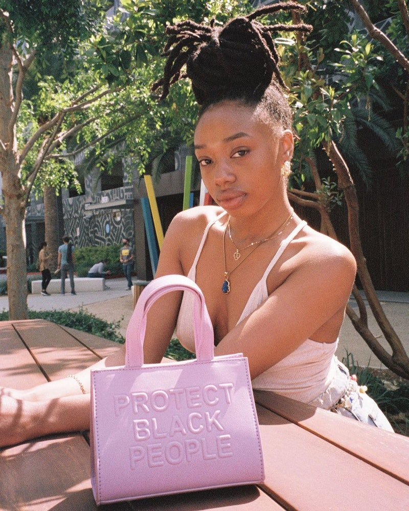 """Model carrying a """"Protect Black People"""" CISE bag."""