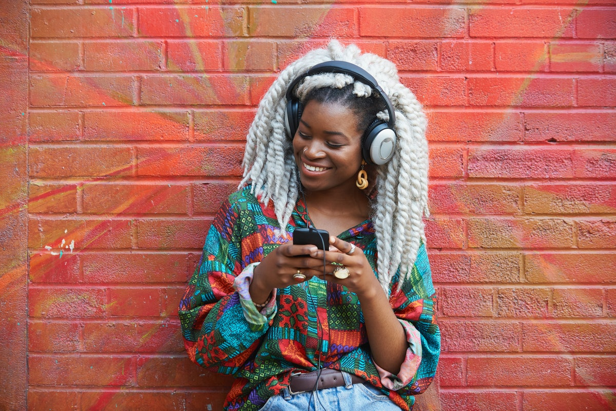 Happy young woman holding her phone, having the best week of June 7, 2021, per her zodiac sign.