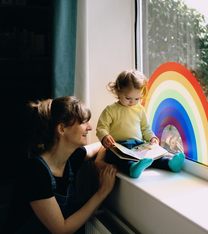 woman and child reading a children's book on windowsill with rainbow painted on glass