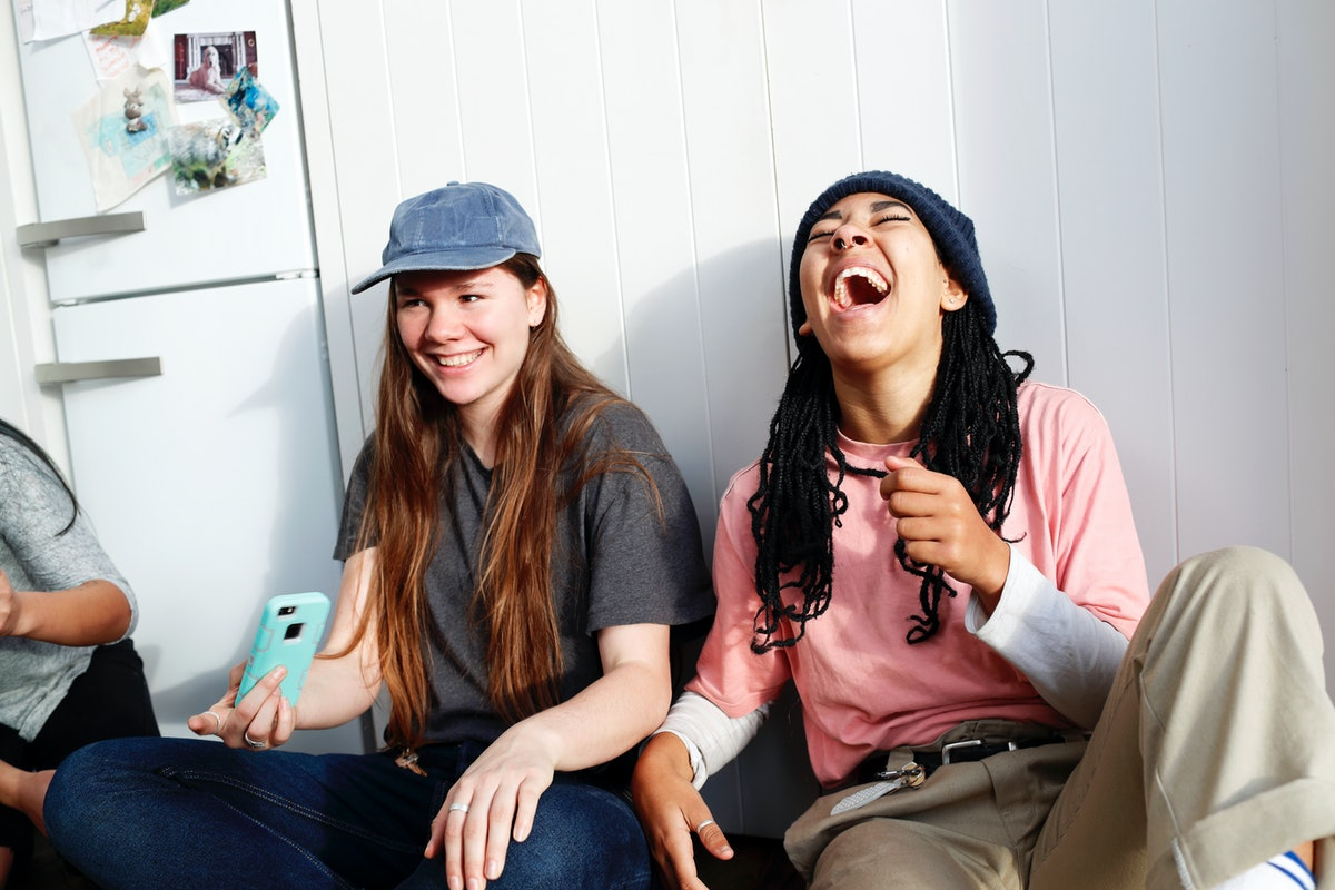 Young women holding phone, commenting funny captions on their friend's Instagram posts.
